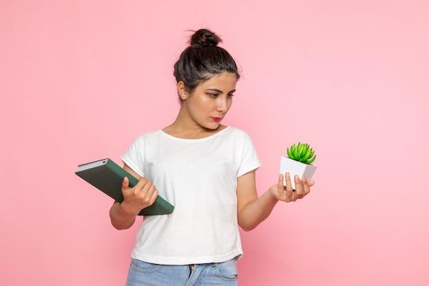 Een vooraanzicht jong wijfje in wit t-shirt en jeans die voorbeeldenboek en installatie houden Gratis Foto