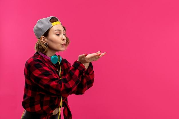 Een vooraanzicht jonge aantrekkelijke vrouw in geruit rood-zwart shirt zwarte broek met blauwe koptelefoon poseren lucht kusjes sturen op de roze achtergrond jonge vrouwelijke mode Gratis Foto