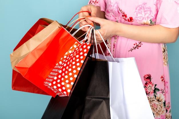 Een vooraanzicht jonge dame in bloem ontworpen roze jurk poseren bedrijf winkelen pakketten op blauw Gratis Foto