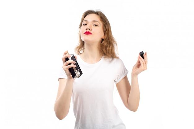 Een vooraanzicht jonge dame in wit t-shirt met zwarte parfum buis op het wit Gratis Foto