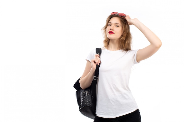 Een vooraanzicht jonge dame in witte t-shirt rode zonnebril zwarte tas op de witte Gratis Foto
