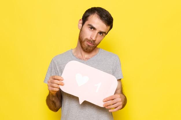 Een vooraanzicht jonge man in grijs t-shirt met wit bord op de gele muur man expressie emotie kleur Gratis Foto