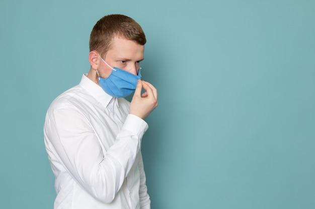 Een vooraanzicht jonge man in wit overhemd en een blauw masker op de blauwe ruimte Gratis Foto