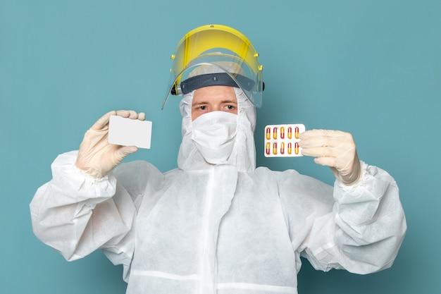 Een vooraanzicht jonge man in wit speciaal pak en gele speciale helm met pillen en witte kaart op de blauwe muur man pak gevaar speciale uitrusting kleur Gratis Foto