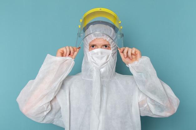 Een vooraanzicht jonge man in wit speciaal pak en gele speciale helm op de blauwe muur man pak gevaar speciale uitrusting kleur Gratis Foto