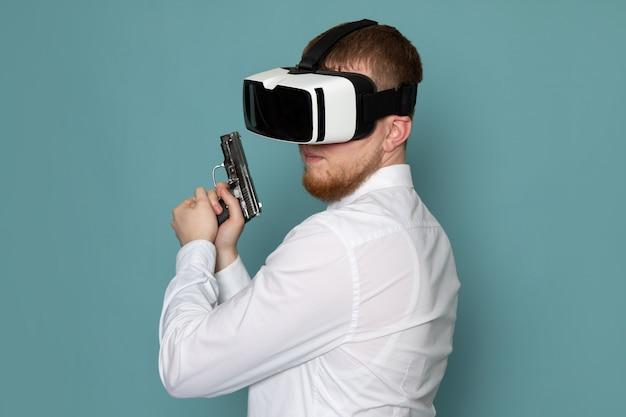 Een vooraanzicht jonge man in wit t-shirt met pistool spelen vr op de blauwe ruimte Gratis Foto