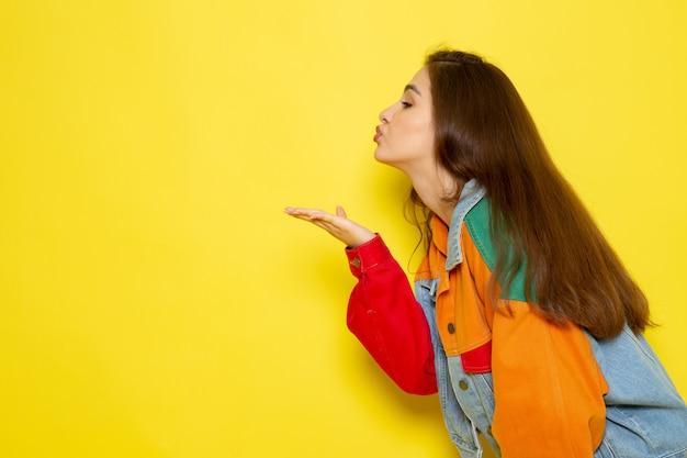 Een vooraanzicht jonge mooie dame in rood shirt en spijkerbroek verzenden luchtkussen Gratis Foto