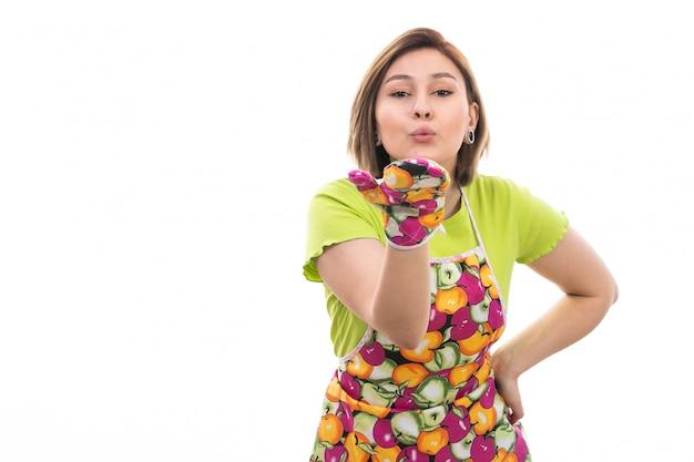 Een vooraanzicht jonge mooie huisvrouw in groene overhemd kleurrijke kaap die luchtkussen op de witte achtergrondhuis schoonmakende keuken verzendt Gratis Foto