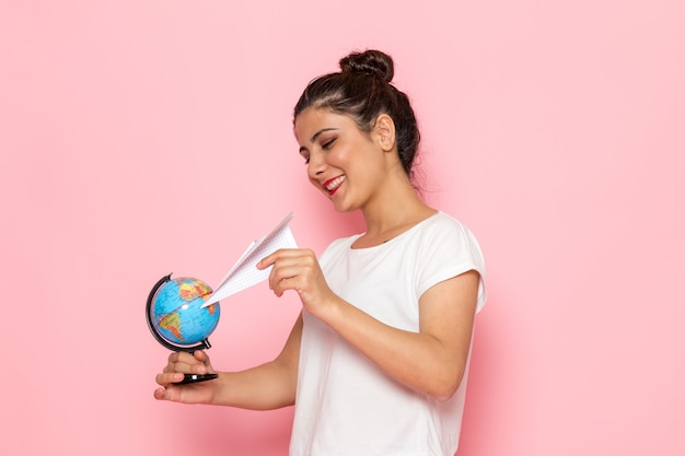 Een vooraanzicht jonge vrouw in wit t-shirt en spijkerbroek met papieren vliegtuigje en kleine wereldbol Gratis Foto