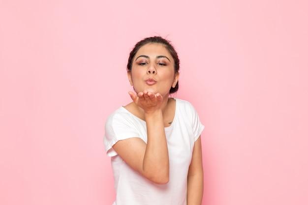 Een vooraanzicht jonge vrouw in wit t-shirt luchtkussen dame emotie gebaar verzenden Gratis Foto