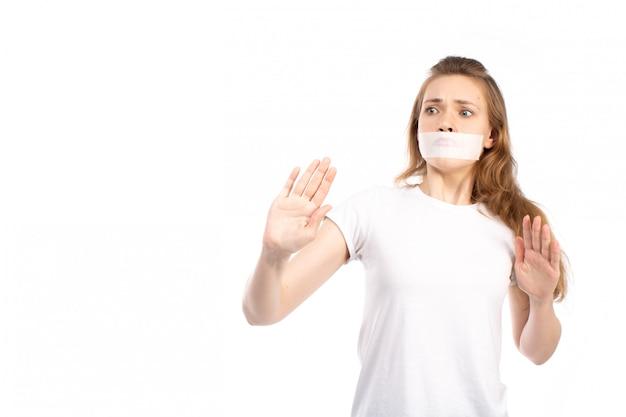Een vooraanzicht jonge vrouw in wit t-shirt met wit verband rond haar mond bang voorzichtig op het wit Gratis Foto