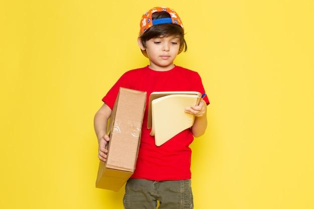 Een vooraanzicht jongetje in rode t-shirt kleurrijke pet en kaki broek met doos op de gele achtergrond Gratis Foto