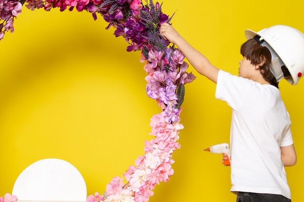 Een vooraanzicht jongetje in wit t-shirt en witte helm versieren bloem staan op het gele bureau Gratis Foto