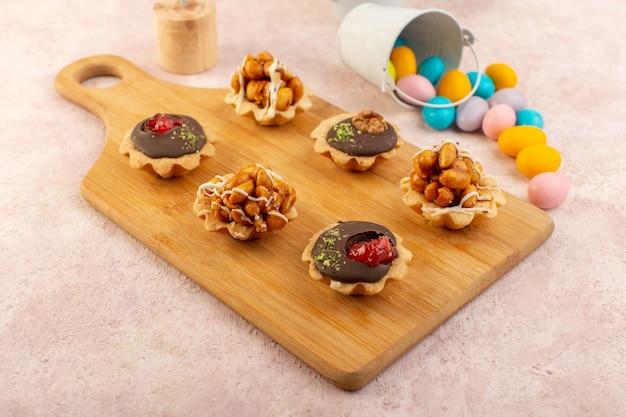 Een vooraanzicht kleine chocoladecake met noten en suikergoed op de kleur van de houten bureau zoete suiker Gratis Foto