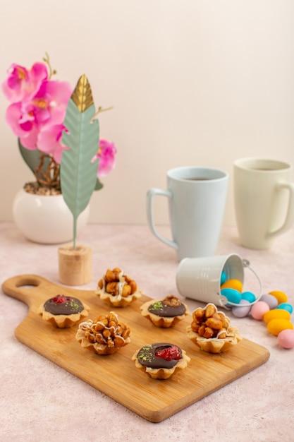 Een vooraanzicht kleine chocoladecake met suikergoed en hete thee op de roze zoete kleur van de bureaucake Gratis Foto