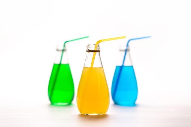 Een vooraanzicht kleurrijke cocktails met rietjes op wit, drink de kleur van de sapcocktail Gratis Foto