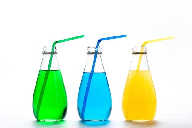 Een vooraanzicht kleurrijke cocktails met rietjes op wit, sap kleur drinken Gratis Foto