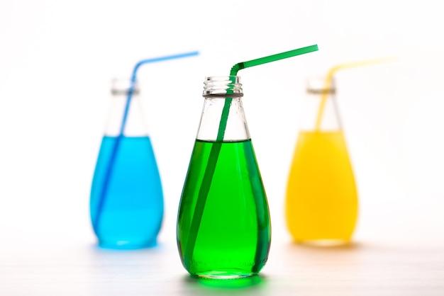 Een vooraanzicht kleurrijke drankjes glazuur en koel met rietjes op wit, drink kleur sap cocktail Gratis Foto