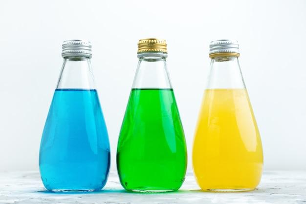 Een vooraanzicht kleurrijke sappen in glazen flessen op wit, sap kleur drinken Gratis Foto