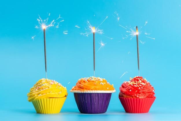Een vooraanzicht kleurrijke taarten heerlijk op blauw, kleur van de verjaardagsviering Gratis Foto