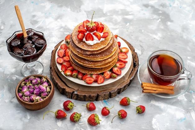 Een vooraanzicht lekkere ronde pannekoeken met room en rode aardbeienthee op de houten bureaucake Gratis Foto
