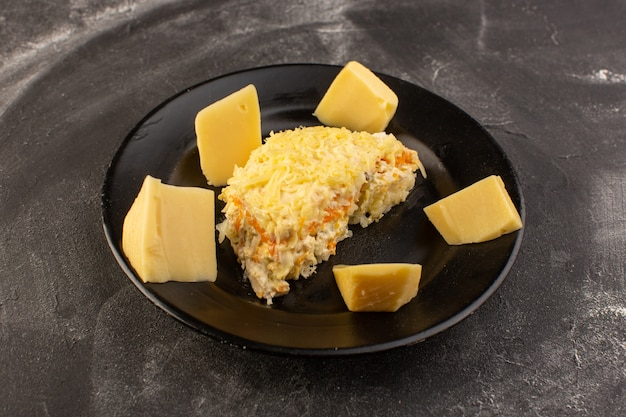 Een vooraanzicht mayyonaised groentesalade met verse kaas binnen zwarte plaat op de grijze het voedselmaaltijd van de lijstsalade Gratis Foto