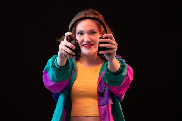 Een vooraanzicht moderne jonge dame in kleurrijke jas oranje t-shirt met zwarte koptelefoon poseren op de zwarte achtergrond dansen moderne mode Gratis Foto