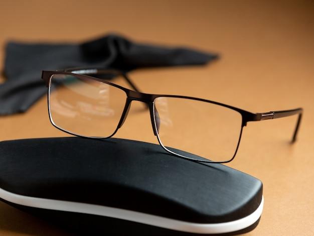 Een vooraanzicht moderne zonnebril modern op de bruine achtergrond geïsoleerde visie bril elegantie Gratis Foto