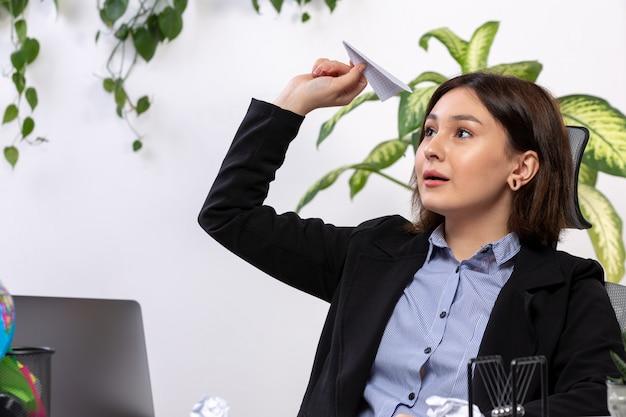 Een vooraanzicht mooie jonge zakenvrouw in zwarte jas en blauw shirt lachend gooien papier vliegtuigen voor tafel zakelijke baan kantoor Gratis Foto