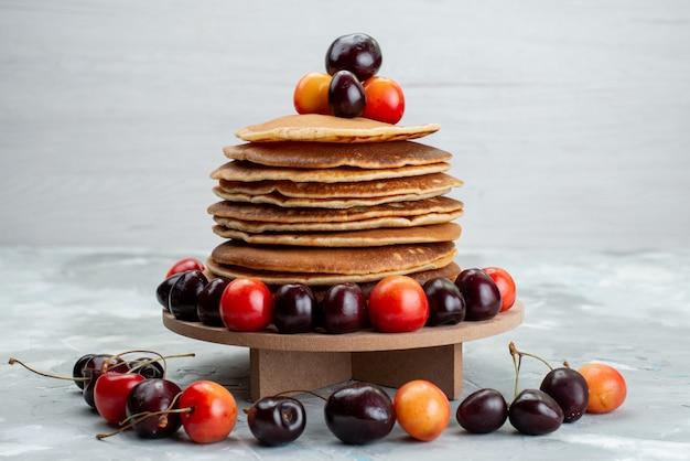 Een vooraanzicht om pannekoeken met kersen op het fruit van de lichte bureaucake Gratis Foto