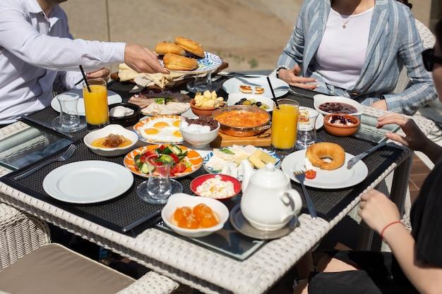 Een vooraanzicht ontbijttafel mensen rond de tafel die hun maaltijd hebben tijdens het ontbijt van de dagmaaltijd Gratis Foto