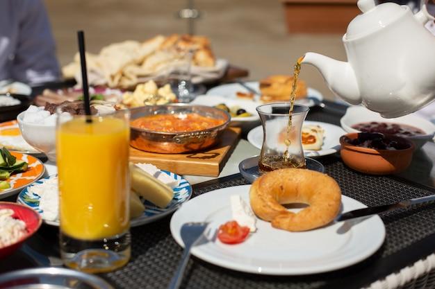 Een vooraanzicht ontbijttafel mensen rond tafel hun maaltijd overdag eten maaltijd ontbijt thee Gratis Foto