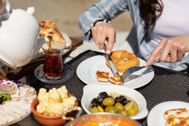 Een vooraanzicht ontbijttafel mensen rond tafel hun maaltijd overdag eten thee ontbijt Gratis Foto