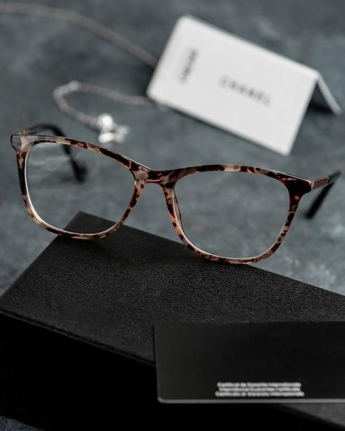 Een vooraanzicht optische zonnebril op het grijze bureau met zilveren armbanden isoleerde zicht visie ogen Gratis Foto