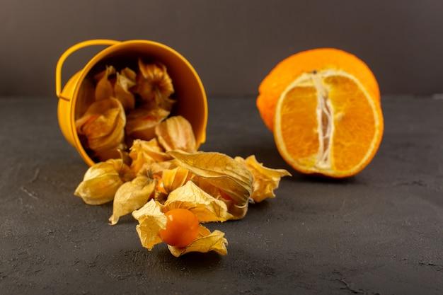 Een vooraanzicht oranje fruit met schillen samen met gesneden en geheel oranje op donker Gratis Foto