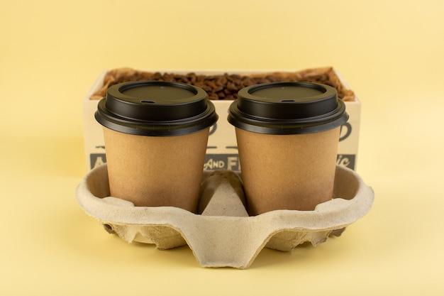 Een vooraanzicht plastic koffie bekers levering koffiepaar op de gele muur Gratis Foto