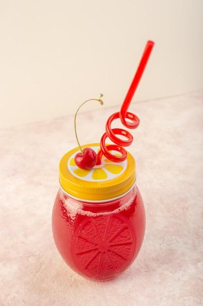 Een vooraanzicht rode kersencocktail vers en suikerglazuur met stro op het roze bureau drinkt het fruit van de sapkleur Gratis Foto