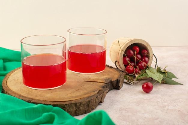 Een vooraanzicht rood kersensap met verse kersen op de roze drank van de het fruitcocktail van de bureaukleur Gratis Foto