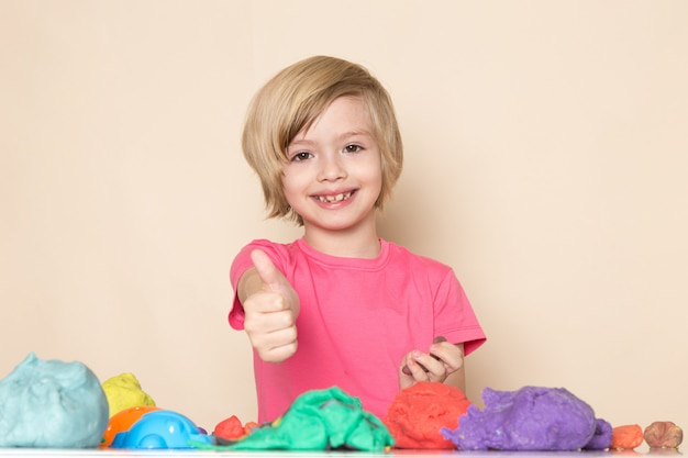 Een vooraanzicht schattig klein kind in roze t-shirt met geweldige teken spelen met kleurrijke kinetisch zand Gratis Foto