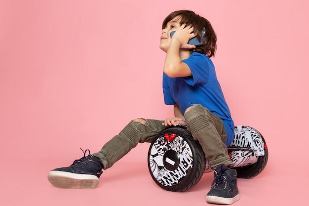 Een vooraanzicht schattige jongen in blauw t-shirt praten aan de telefoon en zittend op de segway roze ruimte Gratis Foto