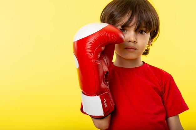 Een vooraanzicht schattige jongen in rode bokshandschoenen en rode t-shirt op de gele muur Gratis Foto