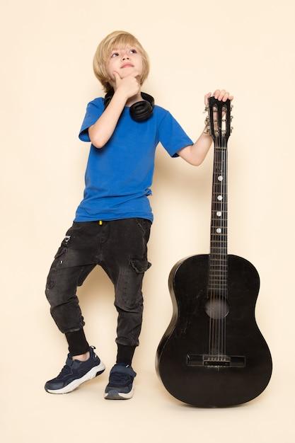Een vooraanzicht schattige kleine jongen in blauw t-shirt met zwarte koptelefoon met zwarte gitaar Gratis Foto