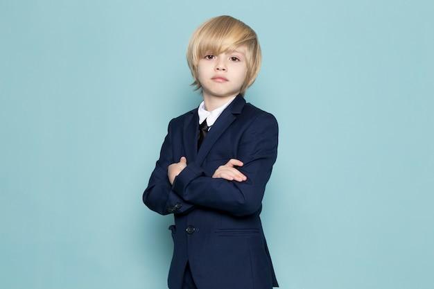 Een vooraanzicht schattige zakelijke jongen in blauwe klassieke pak poseren op zoek naar de camera zakelijke werkmode Gratis Foto