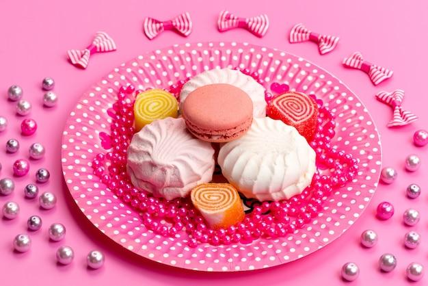 Een vooraanzicht schuimgebakjes en macarons in roze, bord samen met strikken op roze, cake biscuit banketbakkerij Gratis Foto