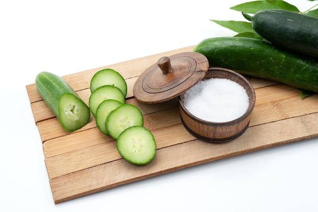Een vooraanzicht sneed komkommers met hele komkommers en zout op bruin houten bureau en witte voedselmaaltijd Gratis Foto