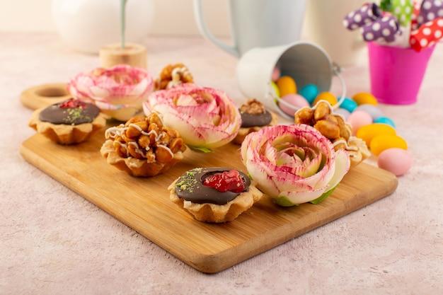 Een vooraanzicht van kleine chooclate cakes met bloemen en kleurrijke snoepjes Gratis Foto
