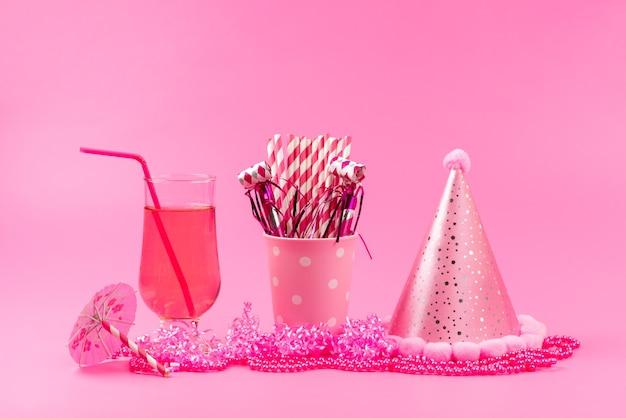 Een vooraanzicht vers sap met stro samen met verjaardagsdop en stoksuikergoed op roze Gratis Foto