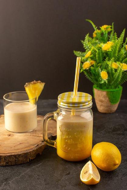 Een vooraanzicht verse cocktail lekker koel drankje binnen kan met stro dichtbij houten bureau samen met citroenen op de donkere achtergrond de zomersap drinken Gratis Foto