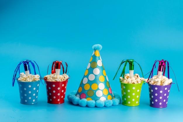 Een vooraanzicht verse popcorn in gekleurde manden samen met een verjaardagskapje op blauw, de snackkorrels van de bioscoopfilm Gratis Foto