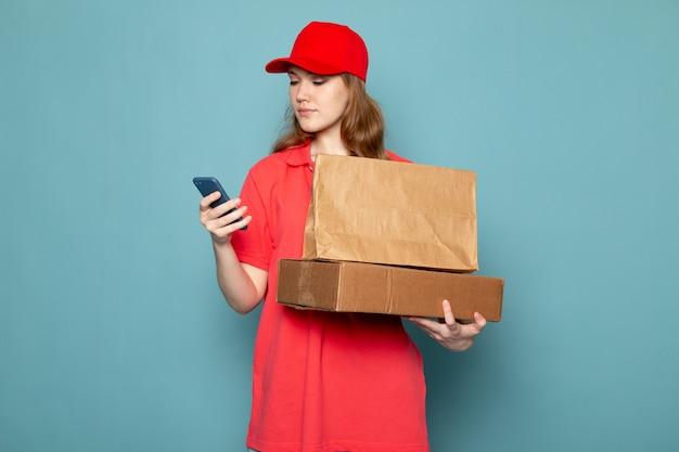 Een vooraanzicht vrouwelijke aantrekkelijke koerier die in rood poloshirt rood glb bruin pakket houden die telefoon met behulp van op de blauwe baan van de achtergrondvoedseldienst Gratis Foto